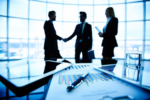 close-up-of-bar-graph-with-executives-negotiating-background_1098-2528